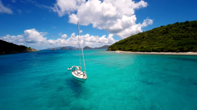 aerial video of a sailboat dropping anchor in the Caribbean video