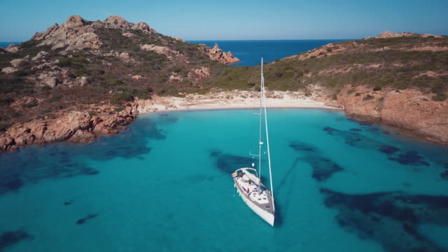 aerial video of a sailing boat in sardinia, incredible island of italy. - sardegna video stock e b–roll