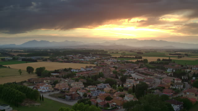 Aerial video of a small town in Costa Brava with Pyrenees in the background at sunset, Catalunya, Spain