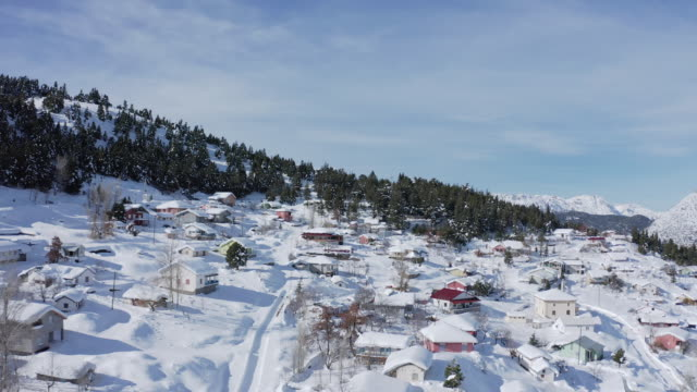 4K aerial video of a village and forest in mountains with covered snow. Taurus Mountains in Turkey.