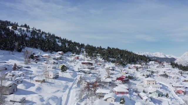 vidéos et rushes de vidéo aérienne 4k d'un village et d'une forêt dans les montagnes avec la neige couverte. montagnes du taureau en turquie. - emballé