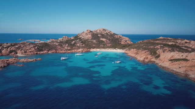 aerial video of boats in front of mortorio island in sardinia, incredible view of the emerald coast in italy - sardegna video stock e b–roll