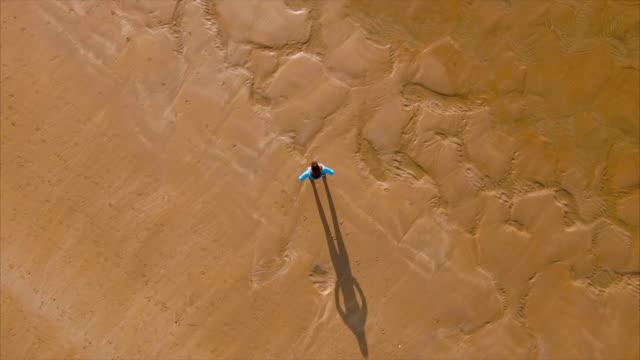 stockvideo's en b-roll-footage met luchtfoto video van fit vrouw staan met de handen op de heupen op strand - handen op de heupen