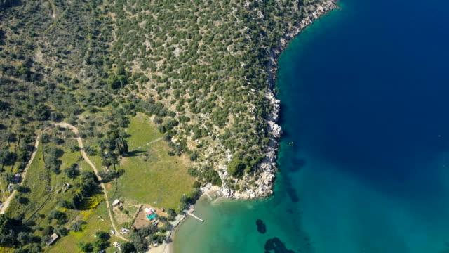 antenn video av grekiska ön poros. vagionia viken. det är blått vatten och kullar. episka panaramic film - poros greece bildbanksvideor och videomaterial från bakom kulisserna