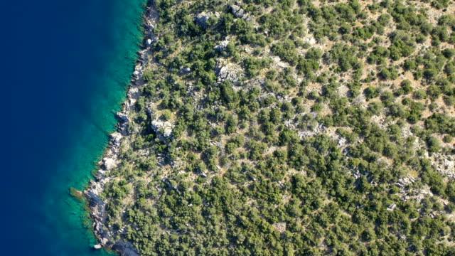 antenn video av grekiska ön poros. vagionia viken. det är blått vatten och kullar. episka panaramic film. 4k - poros greece bildbanksvideor och videomaterial från bakom kulisserna