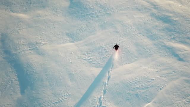 4k uhd antenn video av mannen snöskor i färska pudersnö - djupsnö bildbanksvideor och videomaterial från bakom kulisserna