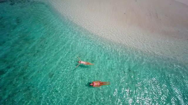 stockvideo's en b-roll-footage met aerial video of women floating at sandy spit, bvi - caraïbische zee