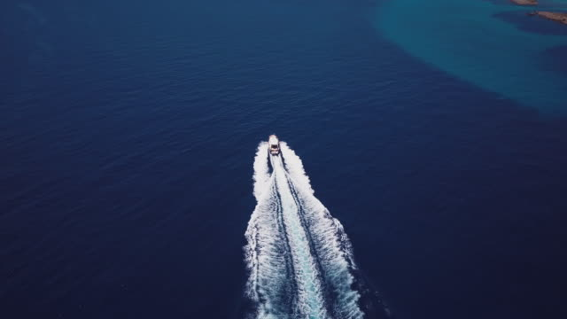 Aerial video shot by a drone of a boat sailing in the Mediterranean Sea. Emerald coast, Sardinia, Italy.