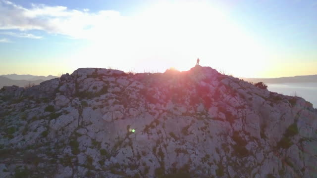 aerial video shot by a drone of a man on the top of the mountain. emerald coast, sardinia, italy. - sardegna video stock e b–roll