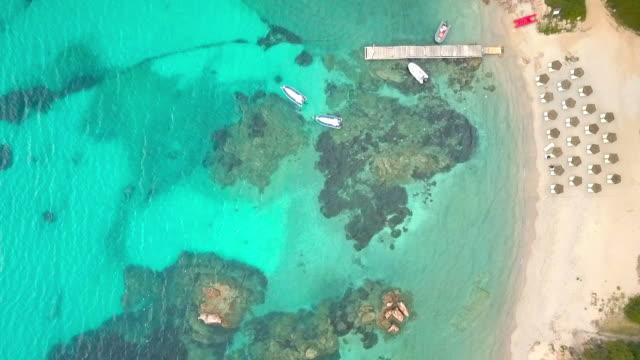 vídeos de stock e filmes b-roll de aerial video shot by a drone of a turquoise sea in italy. beautiful beach of the emerald coast in sardinia. - azul turquesa