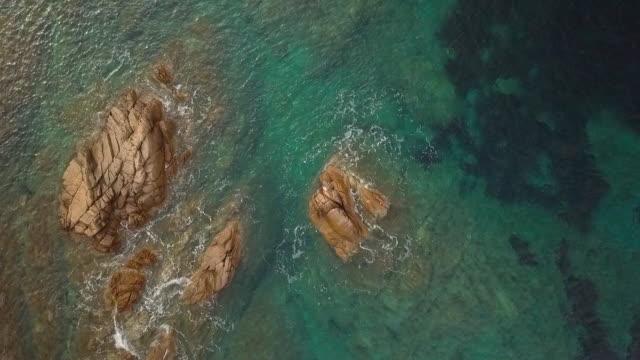 stockvideo's en b-roll-footage met luchtfoto video neergeschoten door een drone van een turquoise zee in italië. mooi strand van de emerald kust in sardinië. - rocks sea