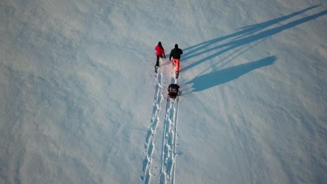 vídeos y material grabado en eventos de stock de familia de vista aérea de video de 4 k con raquetas de nieve al aire libre en invierno al atardecer - viaje a canadá