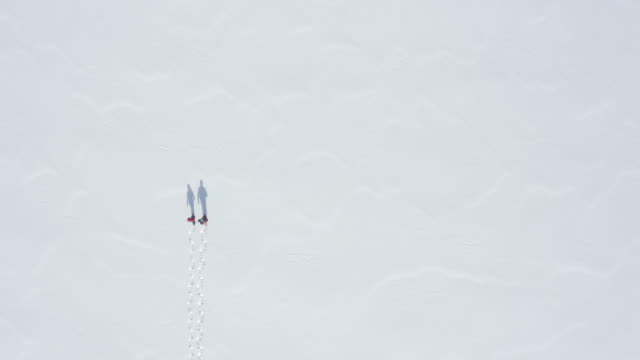 Aerial Video View of a Couple Snowshoeing Outdoor in winter