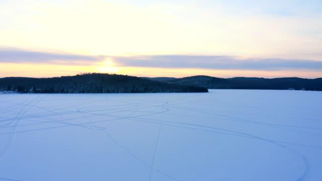 vista video aerea 4k di un lago con traccia di motoslitta sulla neve al tramonto, quebec, canada - brina ghiaccio video stock e b–roll
