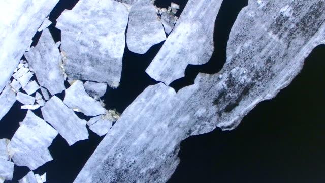 4k. aerial vie. camera goes over a frozen river with broken ice. - ghiaccio galleggiante video stock e b–roll