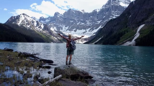 Aerial view 4K- Young woman arms outstretched at mountain lake, hiking trip