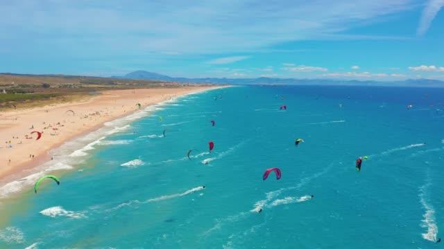 Luftbild. ein großer Strand mit Kitesurfern in Tarifa, Spanien – Video