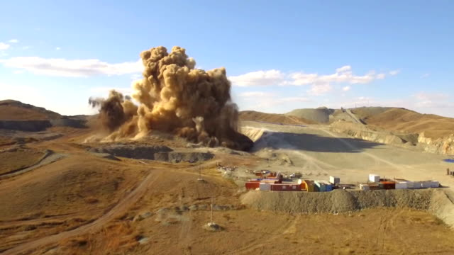 Aerial view A massive explosion rocks in desert. Dirt and metal shards into the air video