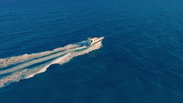 Luftbild. Ein Motorboot, das mit hoher Geschwindigkeit durchs Wasser fährt – Video