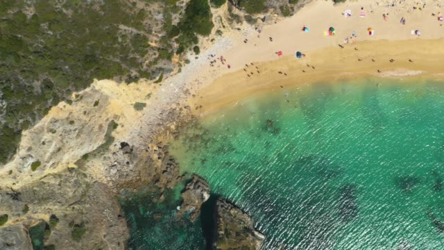 Aerial view a sandy beach line full of bathers and colorful umbrellas