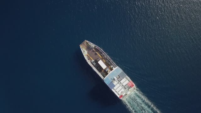 Aerial view above ferry boat with cars driving in the mediterranean sea, Greece.