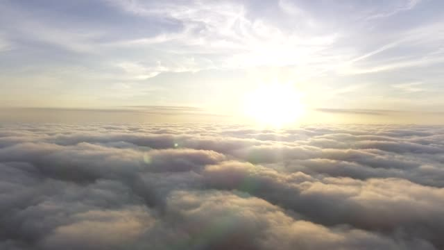 aerial view above the clouds towards the sun - lanuginoso video stock e b–roll