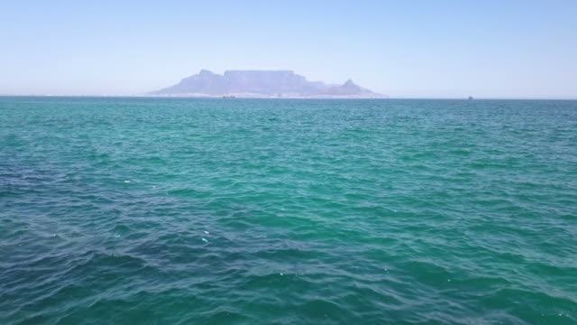 Aerial view across to Table Mountain, Cape Town, South Africa Aerial over the ocean to Table Mountain, Cape Town, South Africa table mountain national park stock videos & royalty-free footage