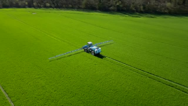 Aerial view Agriculture fertilizer working on farming field, agriculture machinery working on cultivated field and spraying pesticide Aerial view Agriculture fertilizer working on farming field, agriculture machinery working on cultivated field and spraying pesticide cultivated land stock videos & royalty-free footage