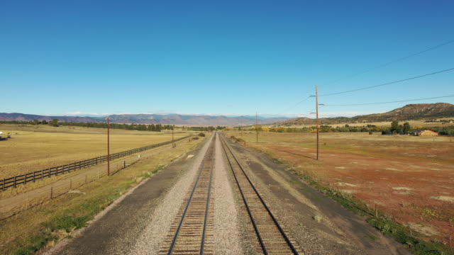 Aerial view along empty railroad tracks leading to the Colorado Rocky Mountain foothills