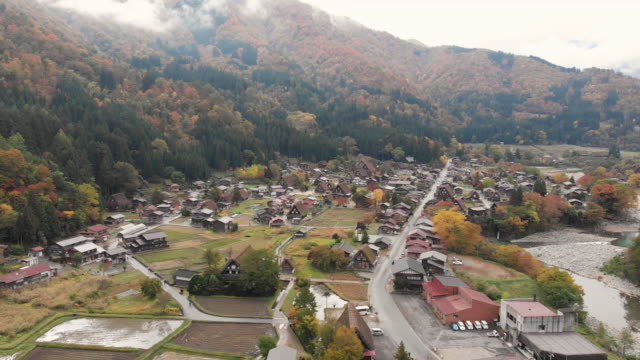 stockvideo's en b-roll-footage met luchtfoto en dolly links van shirakawago dorp in herfst seizoen, gifu, japan. - japan