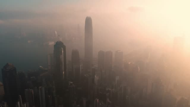 aerial view and dolly left of skyscraper at sunrise in hong kong. - смог над городом стоковые видео и кадры b-roll