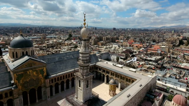 Aerial view around the minaret of the Umayyad Mosque in Syria. Drone is flying around the minaret with the city of Damascus in the background. View over the Umayyad Mosque also known as the Great Mosque of Damascus. One of the largest mosque in the world, the center of Islam religion. We can see over the beautiful and colorful mosque and the minaret with the city of Damascus in the background, under the blue sky. damascus stock videos & royalty-free footage