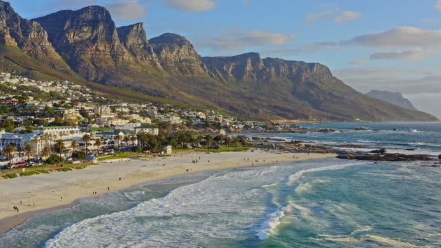 Aerial view at beach in Camps Bay with Twelve Apostles mountain in the background, Cape Town, South Africa Aerial view at beach in Camps Bay with Twelve Apostles mountain in the background, Cape Town, South Africa. south stock videos & royalty-free footage