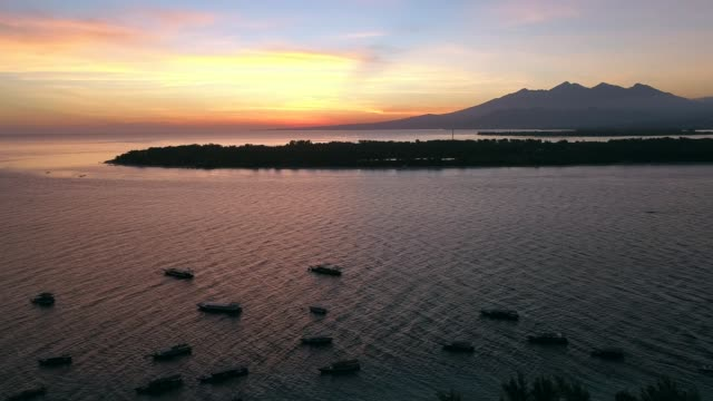 aerial view at group of boats anchored next gili trawangan island during sunset. - group of people стоковые видео и кадры b-roll