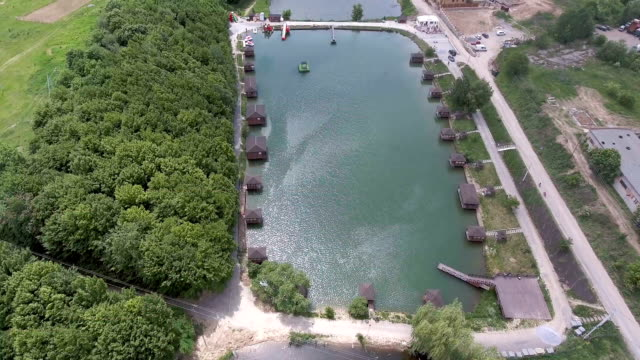 Aerial view at the lake shore. Wooden houses near the water. - vídeo
