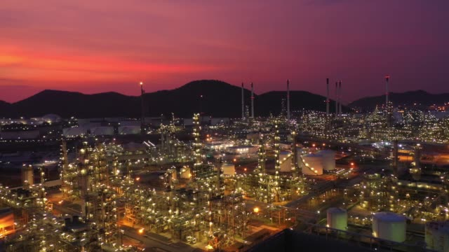 Aerial view at the refinery and oil tank at dusk. Business and petrochemical plants, oil storage tanks and for energy and steel pipes in Twilight time video
