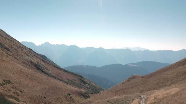 vídeos de stock, filmes e b-roll de vista aérea bela natureza paisagem montanhosa outono com montanhas céu azul claro e grama amarela. tiro de helicóptero voando sobre incrível paisagem natural do vale em dia ensolarado - multicóptero