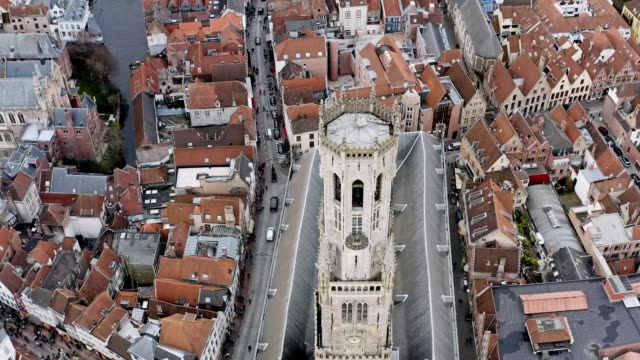 Aerial view Belfry of Bruges medieval bell tower in Belgium Aerial view Belfry of Bruges medieval bell tower iconic gothic church cathedral and panoramic view of Bruges Skyline in Belgium european culture stock videos & royalty-free footage