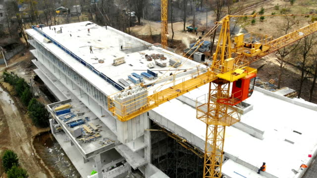 vidéos et rushes de grue de construction de vue aérienne, gros plan. grue de construction sur un fond de bâtiment, fermez vers le haut. - chantier