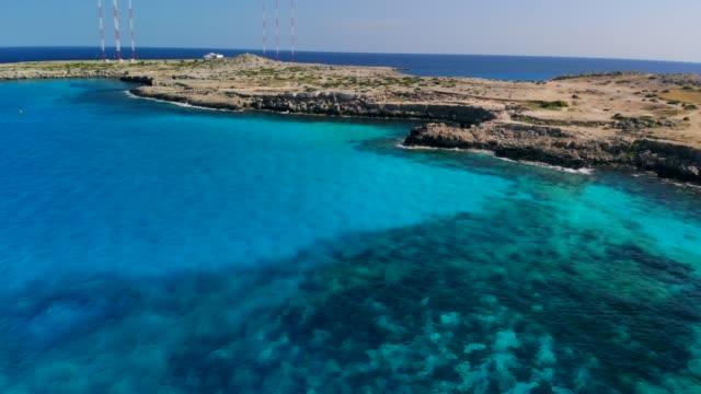 vidéos et rushes de lagon bleu de vue aérienne près du cap cavo greco le jour ensoleillé - baie eau