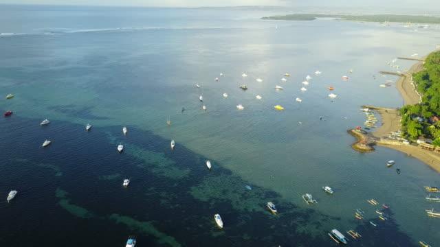 4K: Luftaufnahme von Drohne Footage Mertasari am Strand in Sanur.Some, die traditionellen Fischerboote (Jukung) sind im flachen Wasser geparkt. – Video