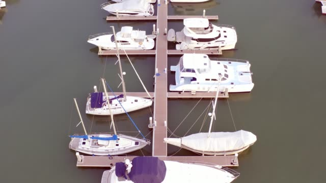 aerial view by drone of yacht club and marina. top view of yacht club. white boats in sea water. marina dock yachts and small moto. yacht and sailboat - molo video stock e b–roll