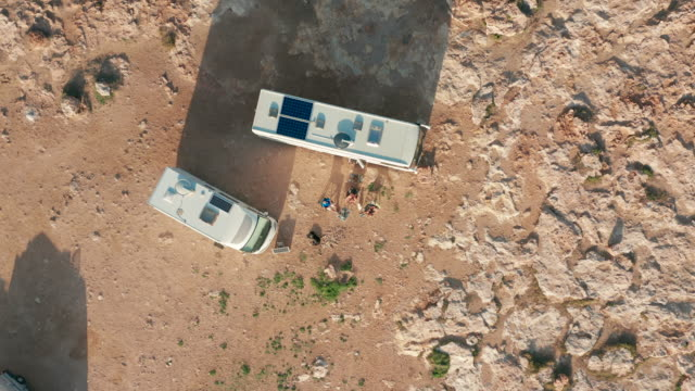 Aerial view. Camping Sites with Modern Motorhome RV Camper Van on a rock near the sea