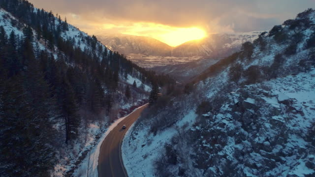Aerial view car driving down snow covered winter road in canyon at sunset video