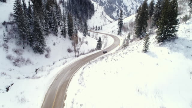 Aerial view car driving down snow covered winter road in canyon video