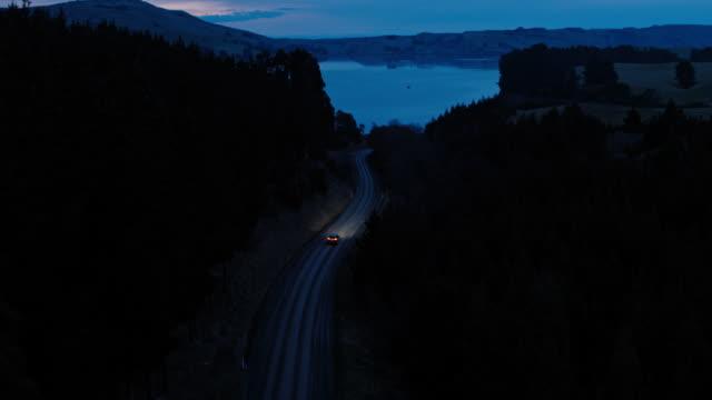 空撮車の田舎道、松の木でヘッドライトと夕暮れ時に駆動 suv の運転 - 電気自動車点の映像素材/bロール