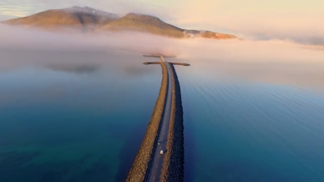 WS Aerial view car moving along road over remote mountain lake,Iceland