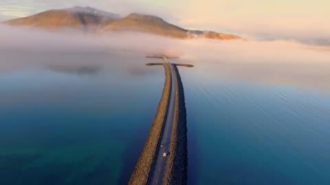 vidéos et rushes de ws voiture vue aérienne se déplaçant le long de la route sur le lac de montagne éloigné, islande - 20 secondes et plus