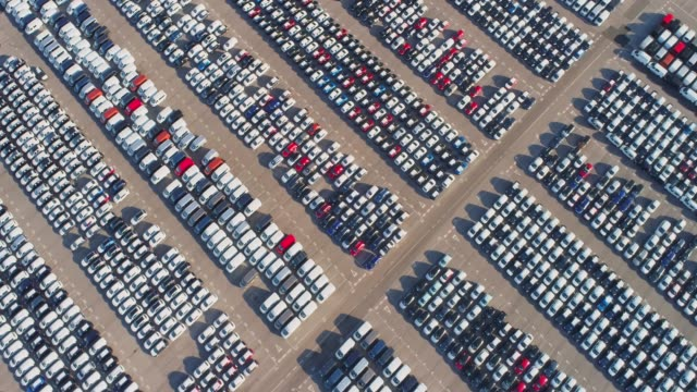 WS Aerial view cars parked in sunny parking lot