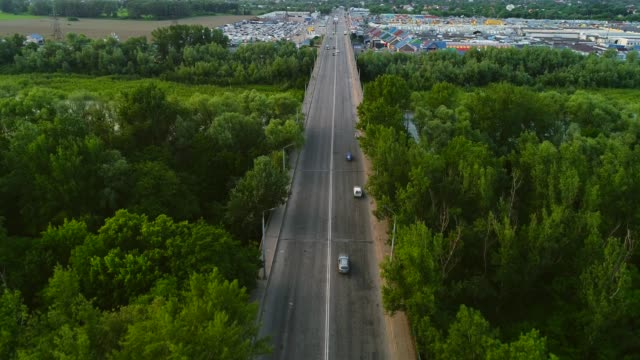 Aerial view city central street, cars, buildings and beautiful nature, which encloses town. 4K.